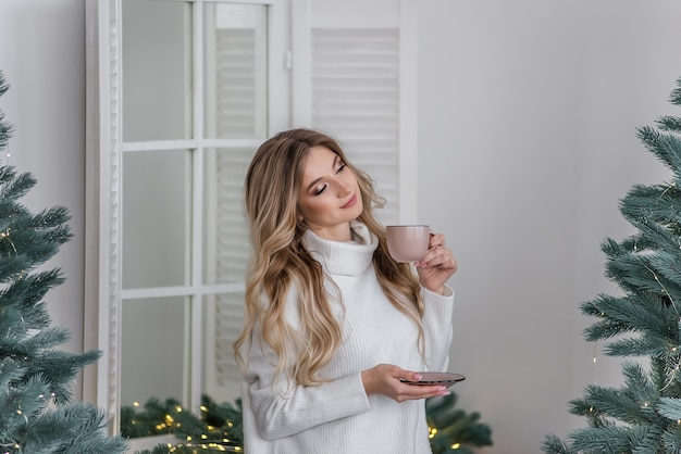 A happy girl in a warm winter sweater stands in a scandinavian-style kitchen and drinks a hot drink from a pink cup by the christmas tree. new year's morning. festive interior and home decoration.