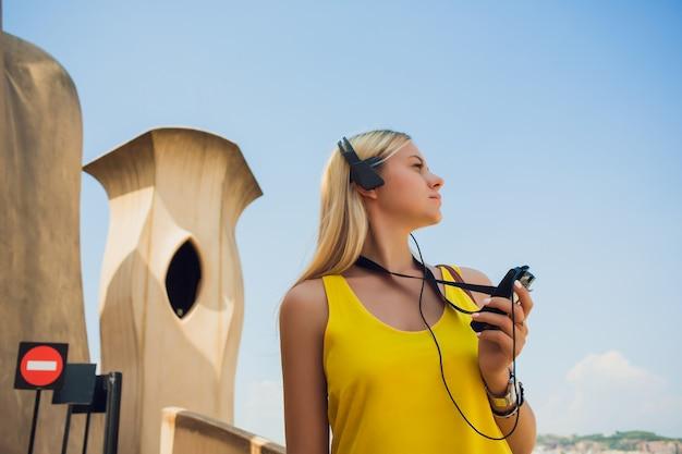 Счастливая девушка нося красную рубашку с большими пальцами руки вверх используя таблетку и слушая музыку с наушниками.