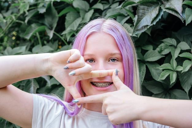 濃い緑のつるの背景に歯のブレースを身に着けている幸せな女の子、矯正ブラケットを身に着けているピンクの髪のかわいい白人の女の子