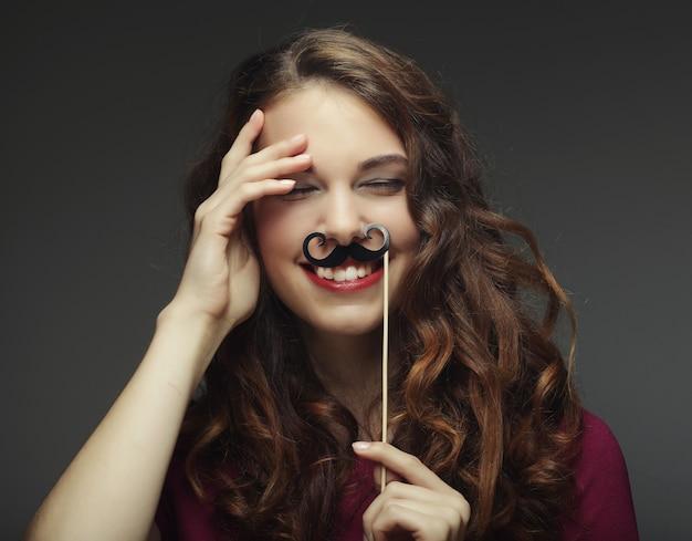 偽の口ひげを生やした幸せな女の子。パーティーの準備ができました。