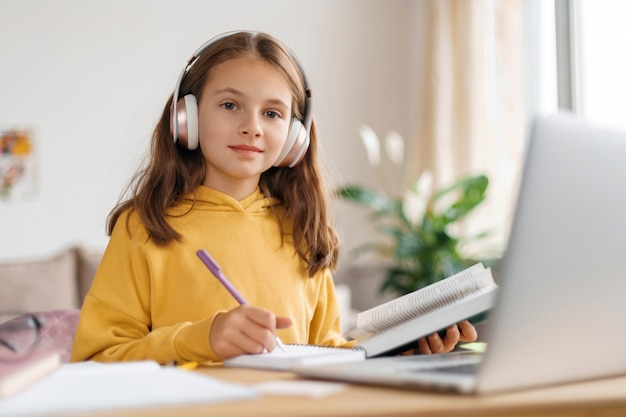 ヘッドフォンを着用し、カメラを見て、ラップトップとインターネットを使用して宿題をしている幸せな女の子。