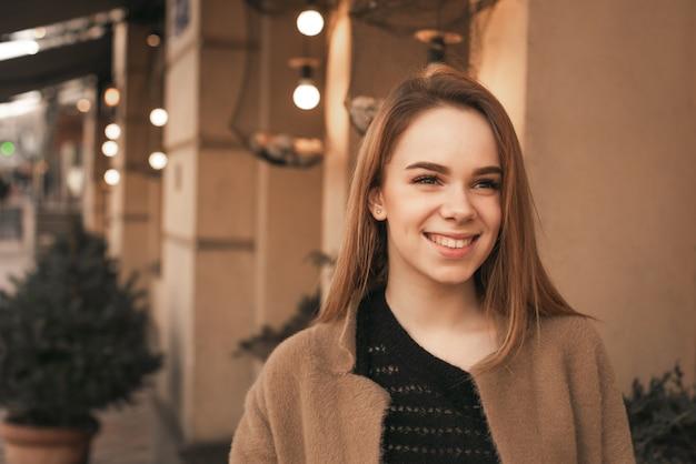 Счастливая девушка носит пальто, стоит на фоне бежевой стены и улицы, смотрит вбок и улыбается