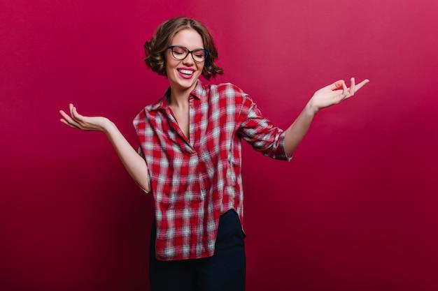 Счастливая девушка носит клетчатую рубашку и черные брюки, позирует с поднятыми руками. портрет расслабленной белой дамы в очках.