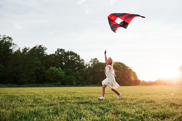 Happy girl in white clothes have fun with kite in the field. beautiful nature.