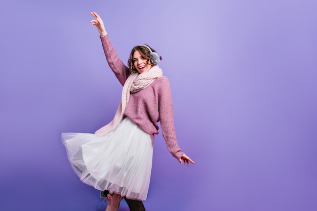 Happy girl in white knitted scarf and fur headphones dancing and waving hands. indoor photo of fashionable caucasian woman wears scarf and winter accessories isolated on purple wall with laugh.