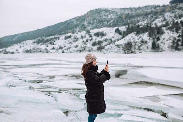 Happy girl in a winter jacket stands against the background of a frozen river and is take the photo at beautiful landscape.