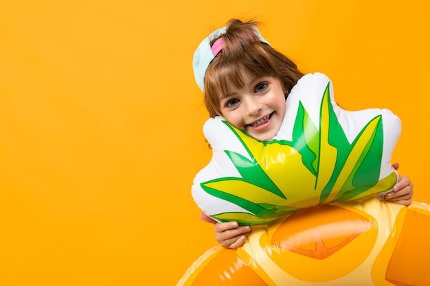 Счастливая девушка с бейсболкой в купальнике с ананасовым резиновым кольцом на оранжевой стене