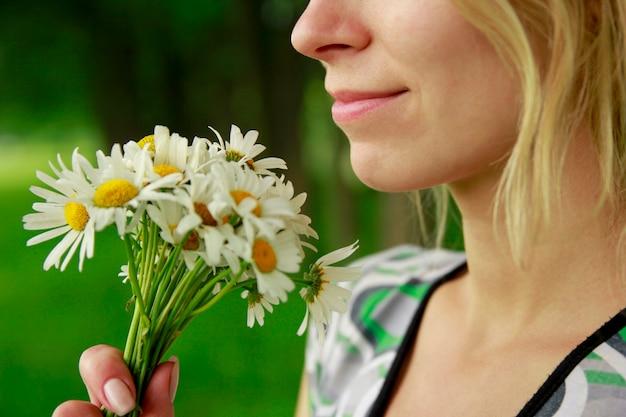 自然公園で花の花束と幸せな女の子
