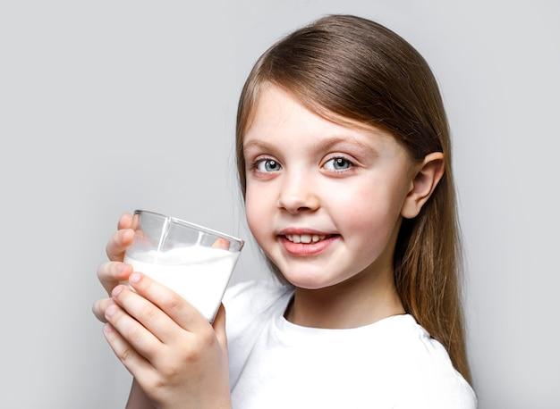 世界の牛乳の日に陽気に笑う牛乳のグラスを持つ幸せな女の子
