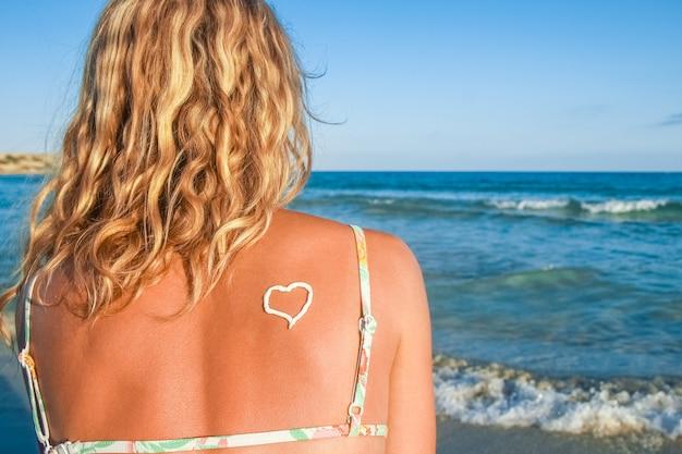 야외에서 바다로 그녀의 뒤에 마음으로 행복 한 소녀