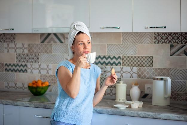 彼女の頭経のタオルの上で幸せな女の子は自宅の彼自身のキッチンで朝食にクッキーとコーヒーを飲む
