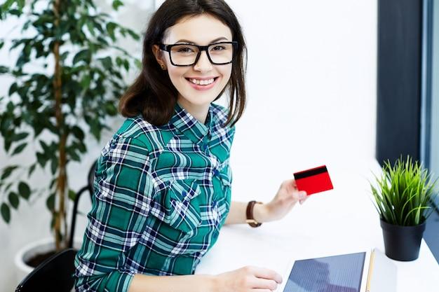タブレットとコーヒー、フリーランスのコンセプト、クレジットカード、オンラインショッピングを持ってカフェに座っているシャツと眼鏡を身に着けている黒髪の幸せな女の子。