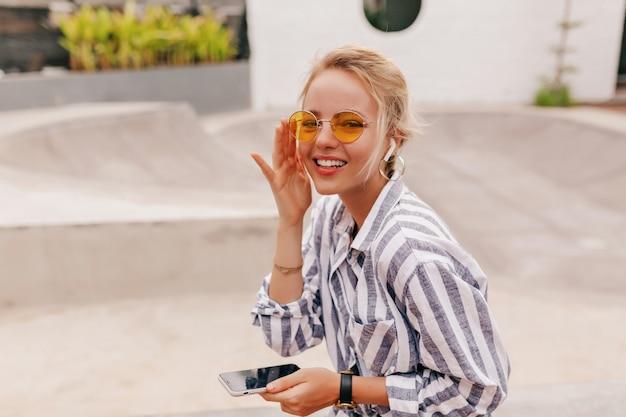 Счастливая девушка со светлыми волосами в оранжевых очках слушает музыку в наушниках