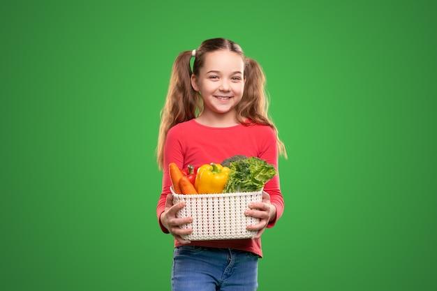 Счастливая девушка с коробкой овощей