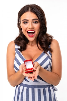 Happy girl with brown hair in a dress with a neckline holds a box with an engagement ring and says yes