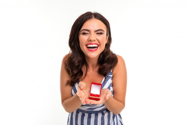 Happy girl with brown hair in a dress with a neckline holds out a box with an engagement ring in hands on a white