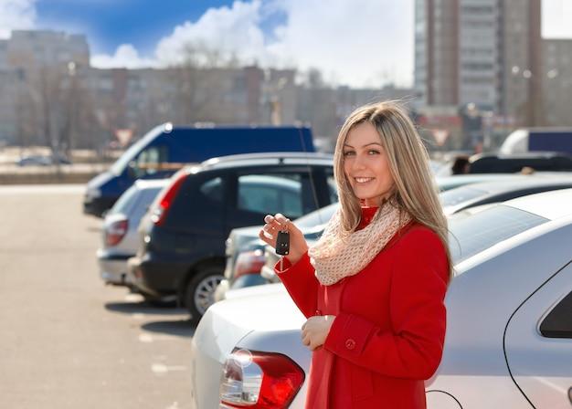 주차장에서 손에 자동차 키와 함께 행복 한 여자