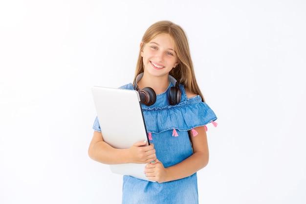 閉じたラップトップとヘッドフォンを首にかけた幸せな女の子