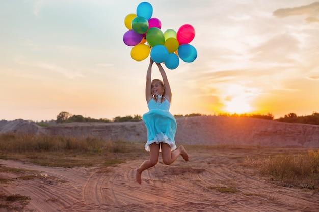 夕暮れ時のカラフルな風船で幸せな女の子