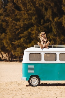 Happy girl with curly hair sitting on mini bus on beach