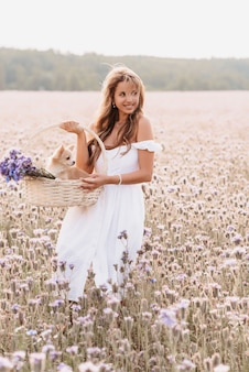 Happy girl with cute chihuahua dog in a basket with a bouquet of flowers in nature in the field in summer