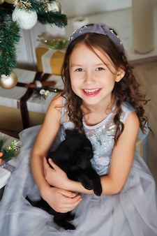 Happy girl with cute griffin breed dog on background of golden beautiful christmas tree with gifts in festive room on merry christmas and happy new year. family warm atmospheric moments with presents