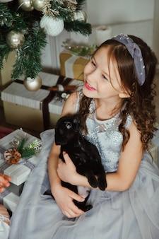 메리 크리스마스와 새해 복 많이 받으세요에 축제 방에 선물과 함께 황금 아름다운 크리스마스 트리 배경에 귀여운 그리핀 품종 개와 함께 행복 한 소녀. 선물과 함께하는 가족 따뜻한 분위기의 순간