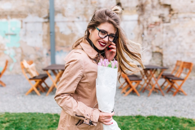 Happy girl with cute hairstyle gladly posing with hair fluttering in the wind and laughing on date. charming woman wearing beige stylish coat holding tulips in front of outdoor cafe on blur background