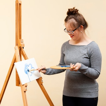 Happy girl with down syndrome painting