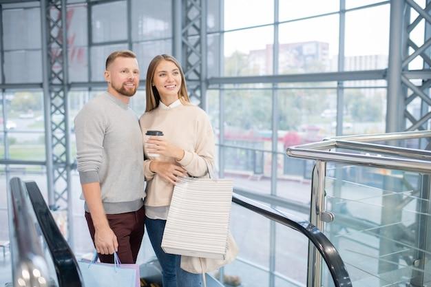 에스컬레이터에 서있는 동안 음료와 가방과 그녀의 남자 친구가 쇼핑몰의 부서 중 하나를보고 행복한 소녀