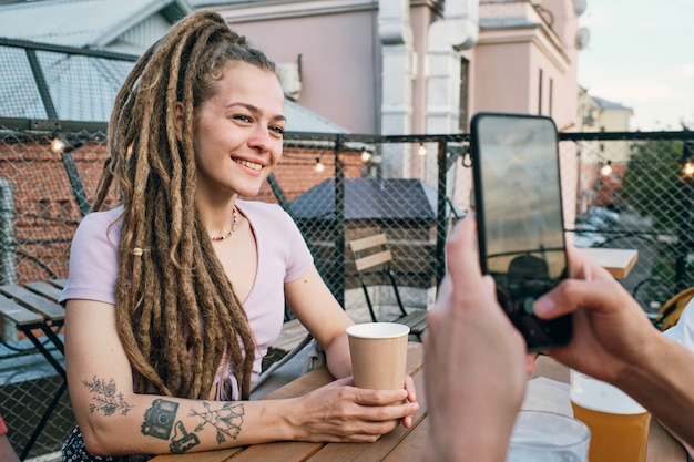 친구가 들고 있는 스마트폰 카메라를 보고 음료수를 마시는 행복한 소녀