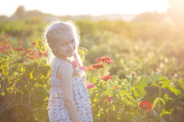 日没時の庭の花と幸せな女の子