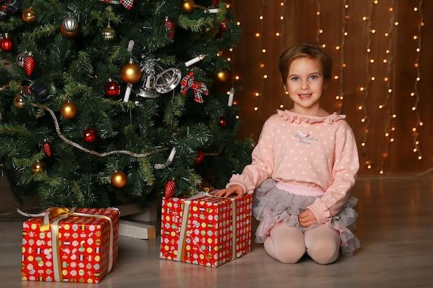 카메라를 보고 선물 상자와 함께 행복 한 소녀입니다.