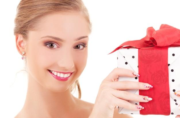 Счастливая девушка с подарочной коробкой над белой стеной