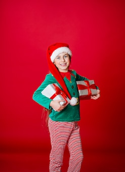 Счастливая девушка с подарками в костюме санта-клауса-помощника эльфа на ярко-красном