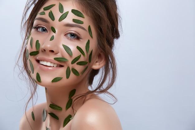 카메라에 미소 짓는 그녀의 몸에 녹색 잎을 가진 행복 소녀