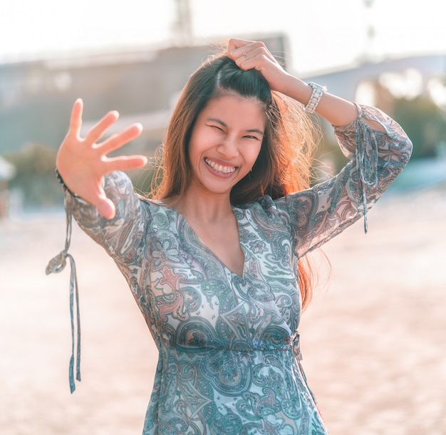 Happy girl with greeting gesture say hi on a beach