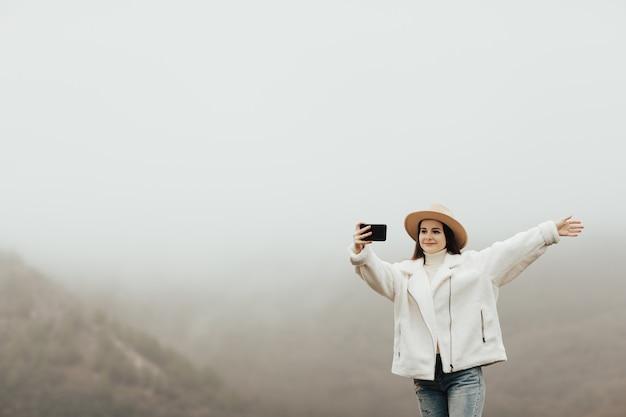 霧の時間に山頂の崖の端でselfieを取る手を持つ幸せな女の子。