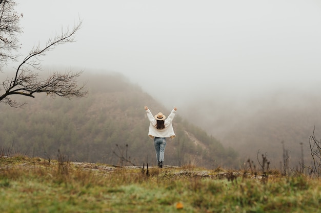 위로 손으로 행복 한 소녀는 안개 산의 목가적 인보기를 즐깁니다.