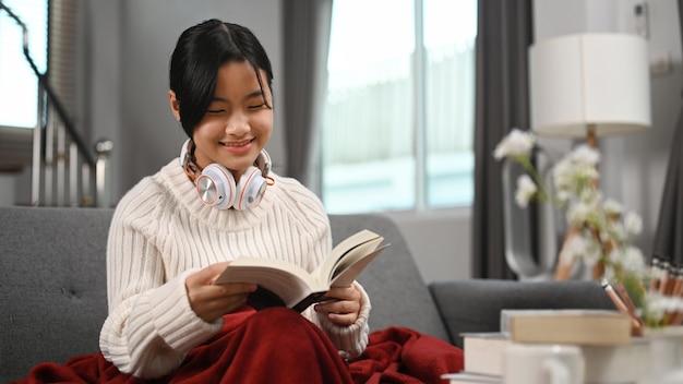 Счастливая девушка с книгой чтения наушников на софе дома.