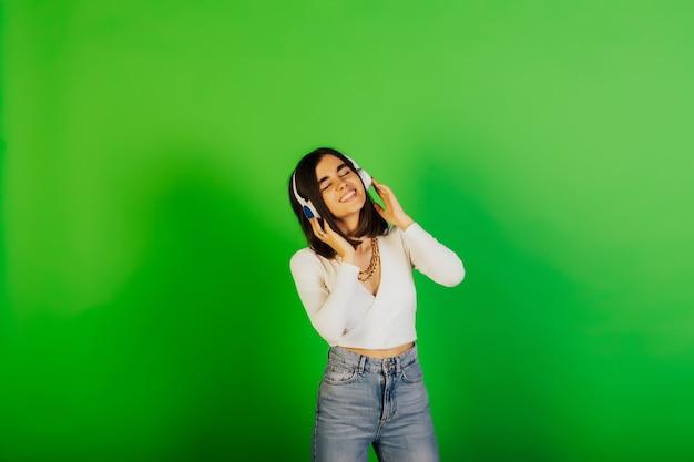 ヘッドフォンを持った幸せな女の子は音楽を聴き、スタジオの緑の表面に目を閉じたままにします。