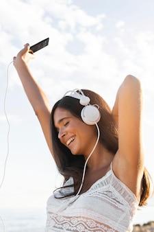 屋外のヘッドフォンで幸せな女の子