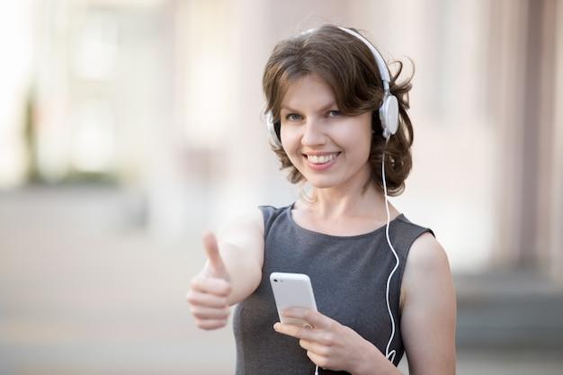 Счастливая девушка с наушниками, показывая позитивный жест
