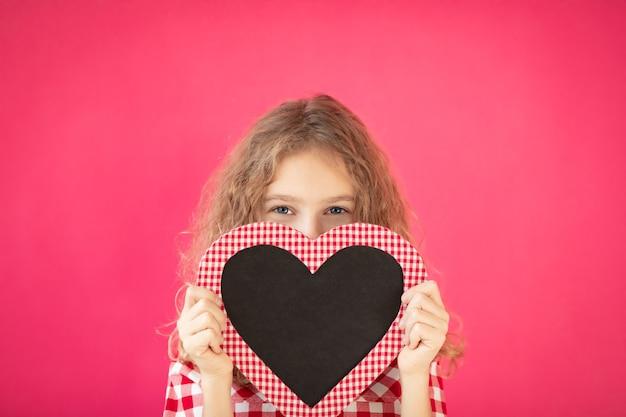 Счастливая девушка с доской в форме сердца на розовом фоне концепции дня святого валентина