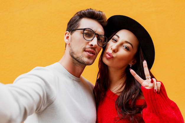 Happy girl with her boyfriend making self portrait by mobile phone. yellow wall. wearing red knitted sweater. new year party mood.
