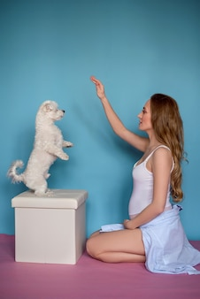 Happy girl with her dog isolated on blue background Premium Photo