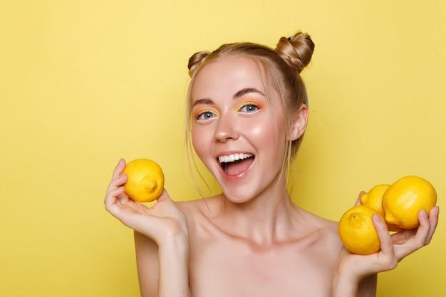 노란색 벽에 레몬과 함께 행복 한 여자