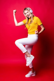 Happy girl with, listening to music in headphones and dancing, holding a smartphone. on a red wall.