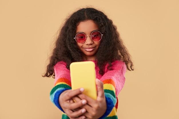 カラフルなニットのセーターとトレンディなサングラスを身に着けている長い巻き毛の幸せな女の子がベージュに対して携帯電話で自分撮りを撮る