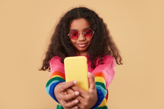 Happy girl with long curly hair wearing colorful knitted sweater and trendy sunglasses taking selfie on mobile phone against beige